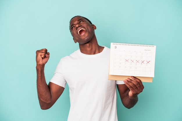 Jeune homme afro-américain tenant un calendrier isolé sur fond bleu levant le poing après une victoire, concept gagnant.