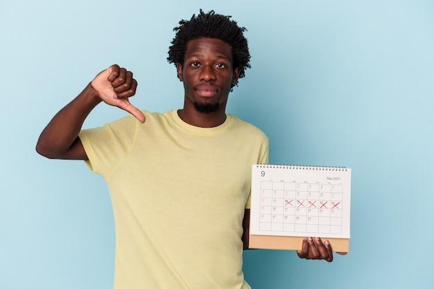 Jeune homme afro-américain tenant un calendrier isolé sur fond bleu montrant un geste d'aversion, les pouces vers le bas. notion de désaccord.