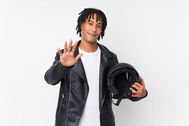 Jeune homme afro-américain tenant un casque de moto isolé sur fond blanc saluant avec la main avec une expression heureuse