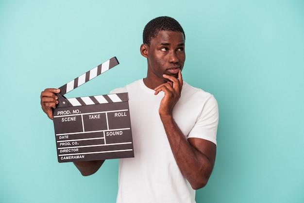 Jeune homme afro-américain tenant un clap isolé sur fond bleu détendu en pensant à quelque chose en regardant un espace de copie.