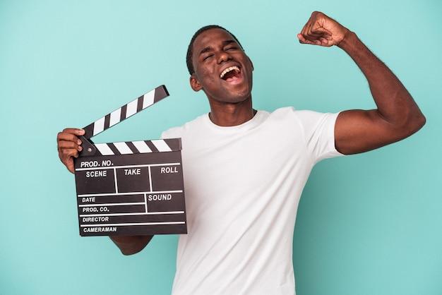 Jeune homme afro-américain tenant un clap isolé sur fond bleu levant le poing après une victoire, concept gagnant.