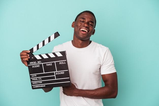 Jeune homme afro-américain tenant un clap isolé sur fond bleu en riant et en s'amusant.