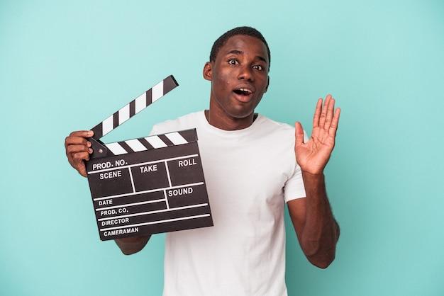 Jeune homme afro-américain tenant un clap isolé sur fond bleu surpris et choqué.