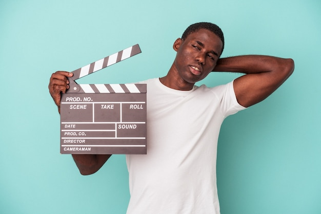 Jeune homme afro-américain tenant un clap isolé sur fond bleu touchant l'arrière de la tête, pensant et faisant un choix.