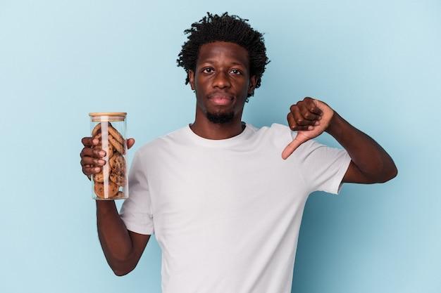 Jeune homme afro-américain tenant des cookies aux pépites de chocolat isolés sur fond bleu montrant un geste d'aversion, les pouces vers le bas. notion de désaccord.