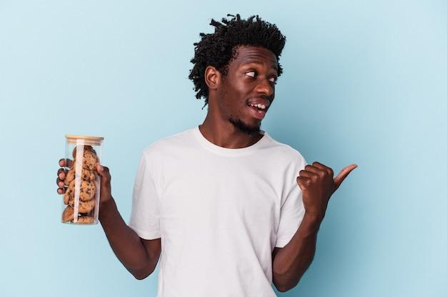 Jeune homme afro-américain tenant des cookies aux pépites de chocolat isolés sur des points de fond bleu avec le pouce loin, riant et insouciant.