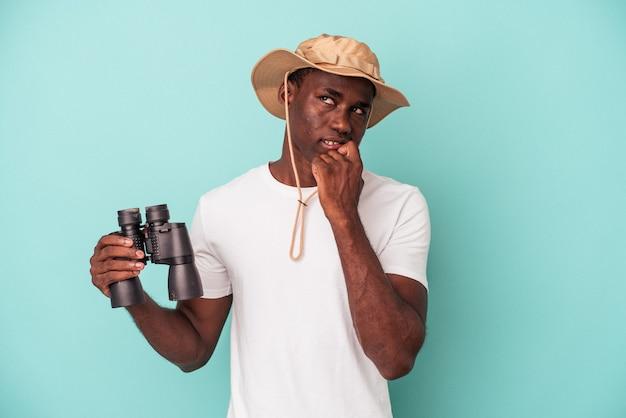 Jeune homme afro-américain tenant des jumelles isolées sur fond bleu détendu en pensant à quelque chose en regardant un espace de copie.