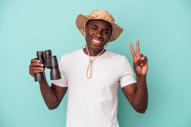 Jeune homme afro-américain tenant des jumelles isolées sur fond bleu joyeux et insouciant montrant un symbole de paix avec les doigts.