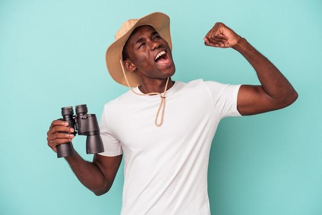 Jeune homme afro-américain tenant des jumelles isolées sur fond bleu levant le poing après une victoire, concept gagnant.