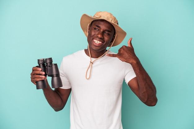Jeune homme afro-américain tenant des jumelles isolées sur fond bleu montrant un geste d'appel de téléphone portable avec les doigts.