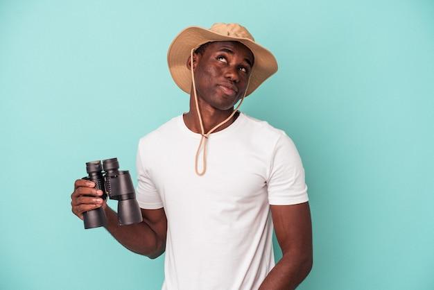 Jeune homme afro-américain tenant des jumelles isolées sur fond bleu rêvant d'atteindre des objectifs et des buts