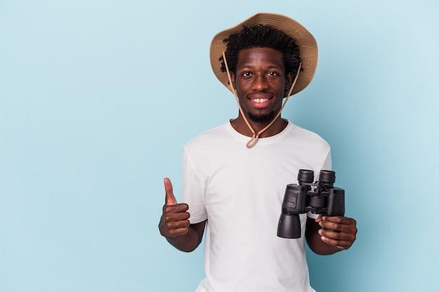 Jeune homme afro-américain tenant des jumelles isolées sur fond bleu souriant et levant le pouce vers le haut