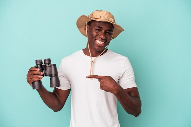 Jeune homme afro-américain tenant des jumelles isolées sur fond bleu souriant et pointant de côté, montrant quelque chose dans un espace vide.