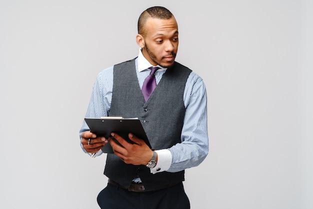 Un jeune homme afro-américain tenant une tablette et un stylo.