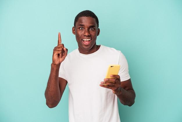 Jeune homme afro-américain tenant un téléphone portable isolé sur fond bleu ayant une bonne idée, concept de créativité.