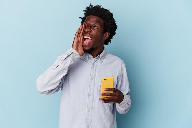 Jeune homme afro-américain tenant un téléphone portable isolé sur fond bleu criant et tenant la paume près de la bouche ouverte.
