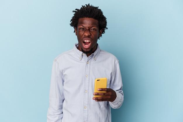 Jeune homme afro-américain tenant un téléphone portable isolé sur fond bleu criant très en colère et agressif.