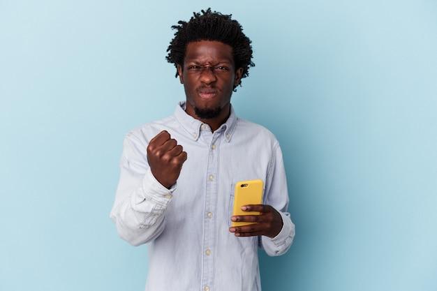 Jeune homme afro-américain tenant un téléphone portable isolé sur fond bleu montrant le poing à la caméra, expression faciale agressive.