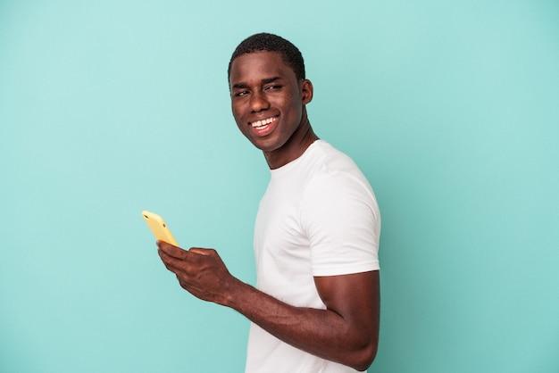 Jeune homme afro-américain tenant un téléphone portable isolé sur fond bleu regarde de côté souriant, joyeux et agréable.