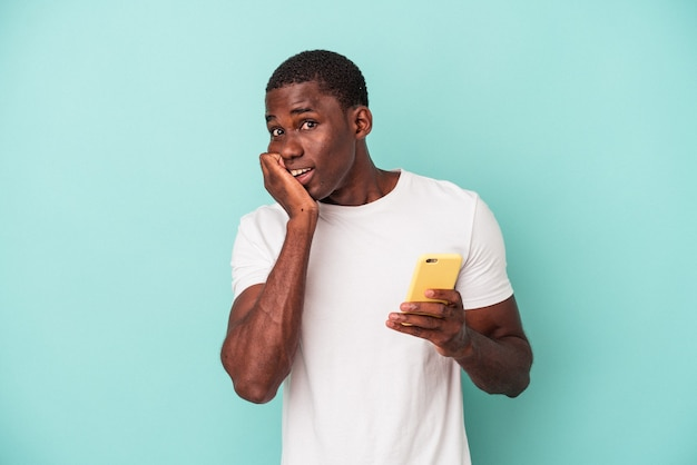 Jeune homme afro-américain tenant un téléphone portable isolé sur fond bleu se rongeant les ongles, nerveux et très anxieux.