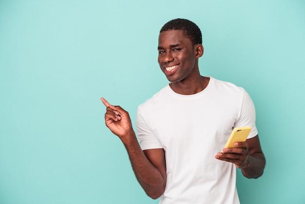 Jeune homme afro-américain tenant un téléphone portable isolé sur fond bleu souriant et pointant de côté, montrant quelque chose dans un espace vide.