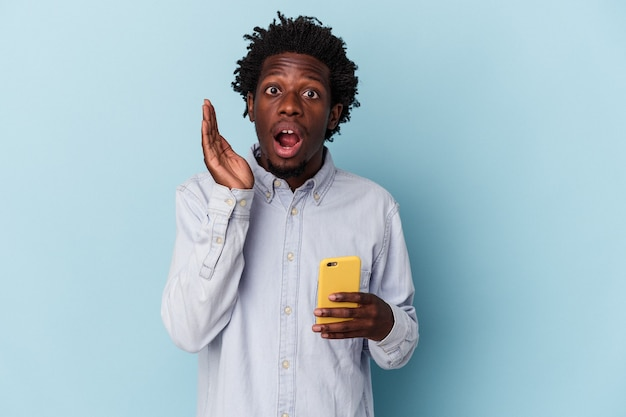 Jeune homme afro-américain tenant un téléphone portable isolé sur fond bleu surpris et choqué.
