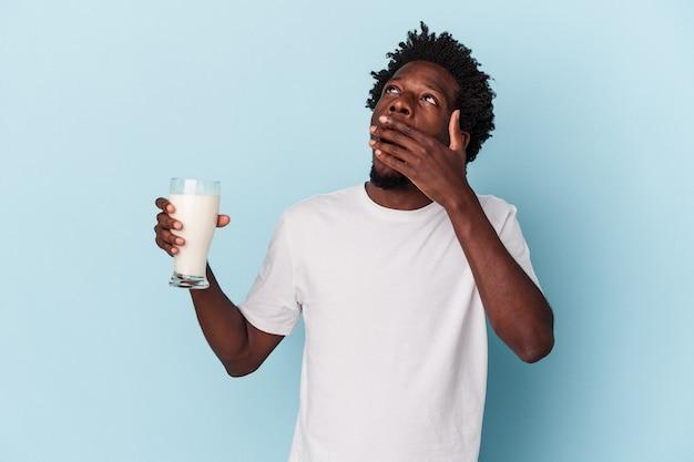 Jeune homme afro-américain tenant un verre de lait isolé sur fond bleu