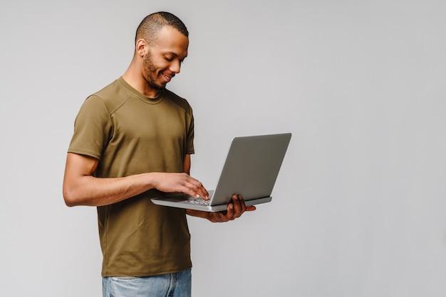 Un jeune homme afro-américain travaillant avec un ordinateur portable