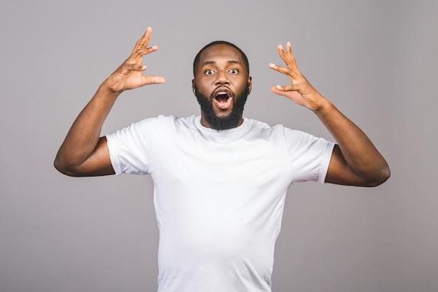 Jeune homme afro-américain très heureux et excité, expression gagnante célébrant la victoire en criant avec un grand sourire et les mains levées isolé sur fond gris.