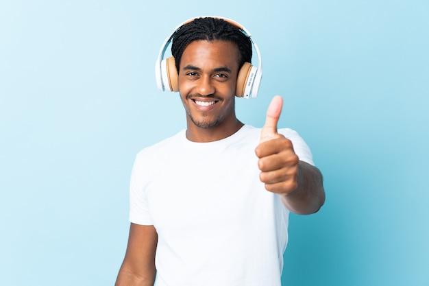 Jeune homme afro-américain avec des tresses isolé sur fond bleu à l'écoute de la musique et avec le pouce vers le haut