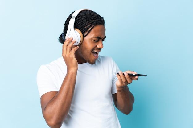 Jeune homme afro-américain avec des tresses isolé sur fond bleu, écouter de la musique avec un mobile et chanter
