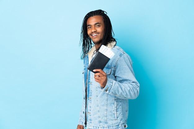 Jeune homme afro-américain avec des tresses isolé sur fond bleu heureux en vacances avec passeport et billets d'avion