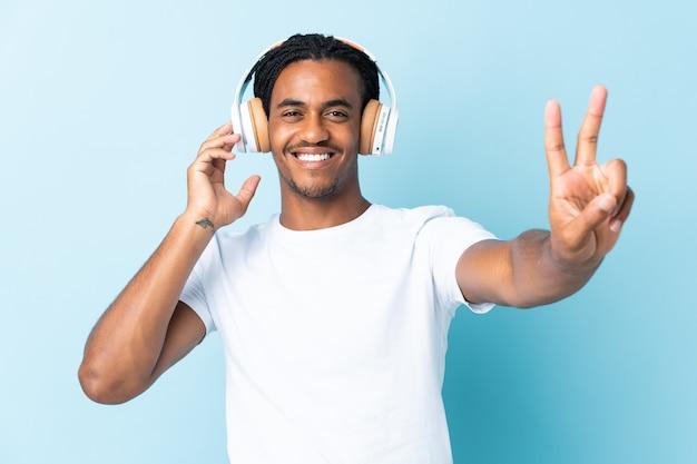 Jeune homme afro-américain avec des tresses isolé sur mur bleu écoute de la musique et du chant