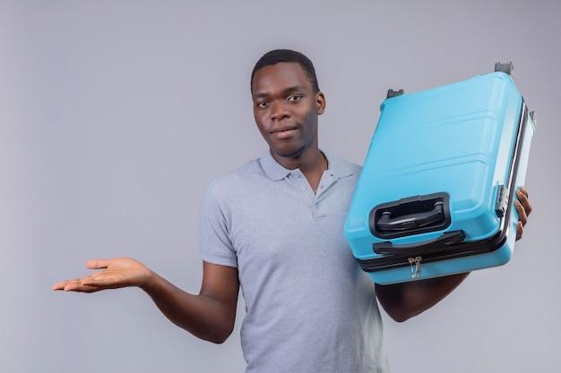 Jeune homme afro-américain voyageur en polo gris tenant une valise bleue présentant avec le bras de sa main à la confiance