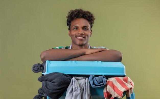 Jeune homme afro-américain voyageur avec valise pleine de vêtements regardant la caméra en souriant, positif et heureux sur fond vert