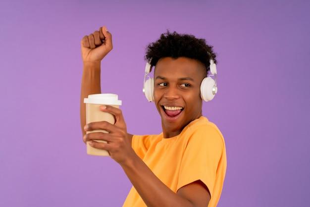 Jeune homme afro appréciant écouter de la musique avec des écouteurs tout en tenant une tasse de café à emporter sur fond isolé.