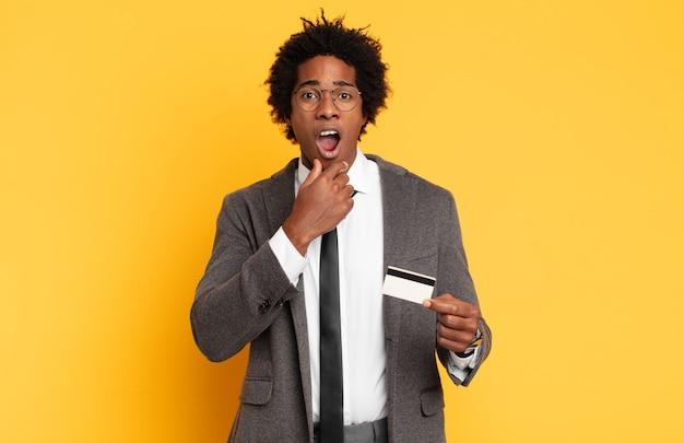 Jeune homme afro avec la bouche et les yeux grands ouverts et la main sur le menton, se sentant désagréablement choqué, disant quoi ou wow