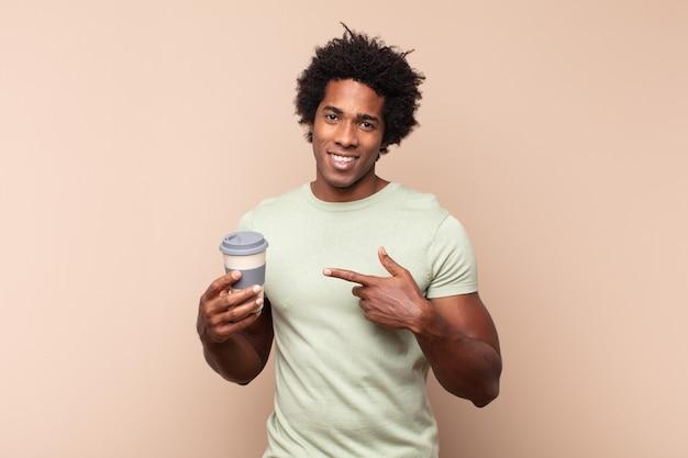 Jeune homme afro à excité et surpris en pointant vers le côté et vers le haut pour copier l'espace