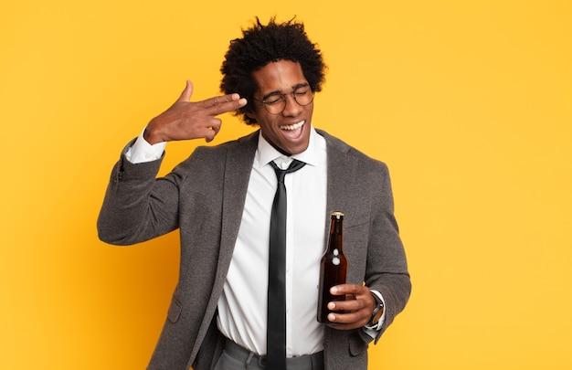 Jeune homme afro noir à l'air malheureux et stressé, geste de suicide faisant un signe d'arme à feu avec la main, pointant vers la tête