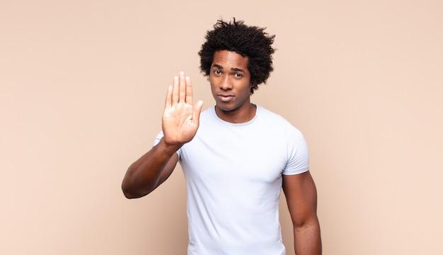 Jeune homme afro noir à l'air sérieux, malheureux, en colère et mécontent interdisant l'entrée ou disant stop avec les deux paumes ouvertes