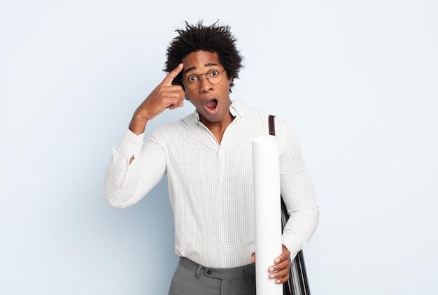 Jeune homme afro noir ayant l'air surpris, bouche bée, choqué, réalisant une nouvelle pensée, idée ou concept