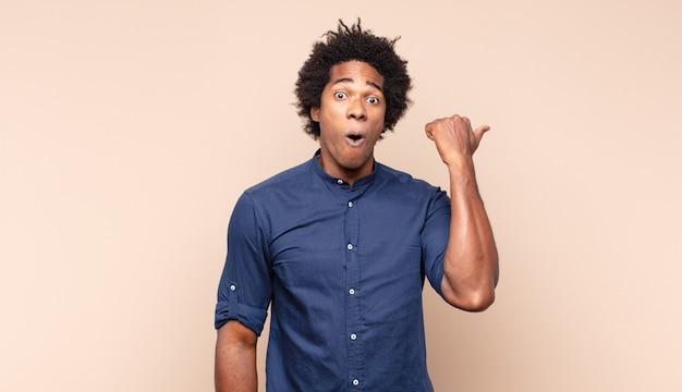 Jeune homme afro noir célébrant un succès incroyable comme un gagnant, l'air excité et heureux en disant: prenez ça!