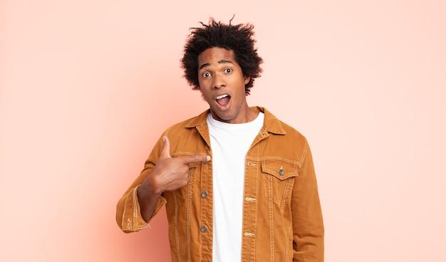 Jeune homme afro noir à la choqué et surpris avec la bouche grande ouverte, pointant vers soi