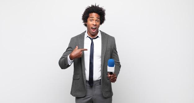 Jeune homme afro noir à choqué et surpris avec la bouche grande ouverte, pointant vers soi