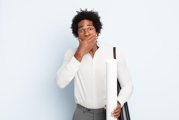 Jeune homme afro noir couvrant la bouche avec les mains avec une expression choquée et surprise, en gardant un secret ou en disant oups