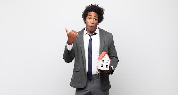 Jeune homme afro noir à l'étonné d'incrédulité, pointant sur l'objet sur le côté et disant wow, incroyable