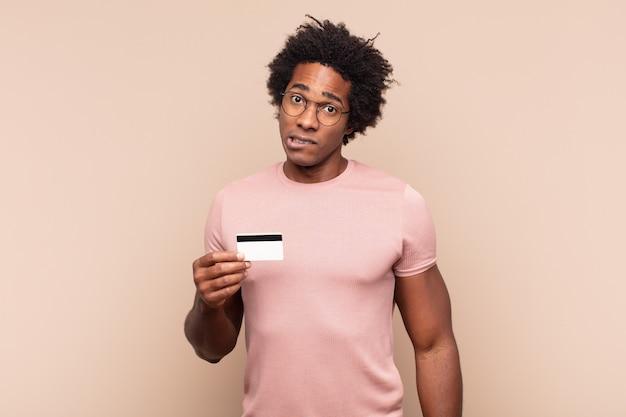 Jeune homme afro noir à la perplexité et à la confusion, mordant la lèvre avec un geste nerveux, ne sachant pas la réponse au problème