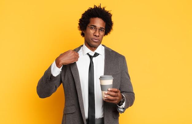 Jeune homme afro noir à la recherche arrogant, réussi, positif et fier, pointant vers soi