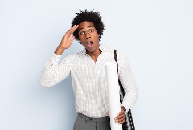 Jeune homme afro noir à la recherche de bonheur, étonné et surpris, souriant et réalisant une bonne nouvelle incroyable et incroyable