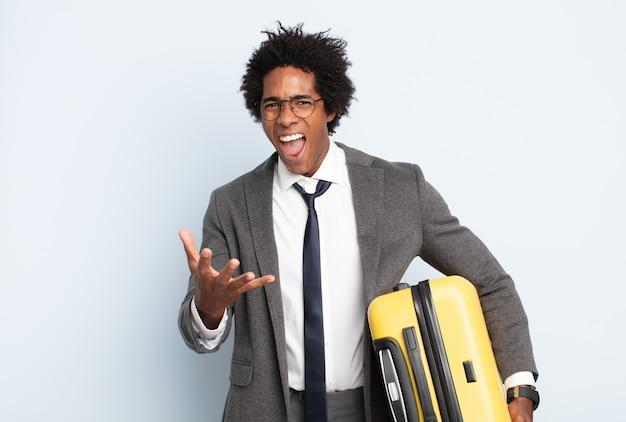 Jeune homme afro noir regardant en colère, ennuyé et frustré hurlant wtf ou ce qui ne va pas avec vous